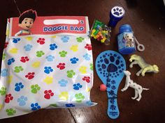 Goody doggy bags for Nate's paw patrol party inside a paw stamp couple of dog figures a paddle ball some bubbles and dog bone candy