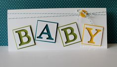 Love the baby blocks!  Use the negative space from cutting out the letters to create the blocks.  Set them on top of the colors of your choice - maybe primary colors - and finish it off with some twine and a button.  DIY baby card