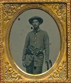 Triple Armed Confederate  1/6 plate ruby  ambrotype of a relaxed standing private with two pistols and a knife in his belt. His hand rests on a nearby chair.