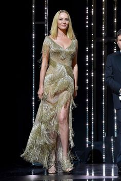 Uma Thurman wearing an Atelier Versace V-neck gold gown At the Closing Ceremony of the 70th annual Cannes Film Festival at Palais des Festivals on May 28, 2017 - HarpersBAZAAR.com