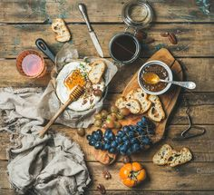 #Cheese fruit and wine set  Cheese fruit and wine set. Camembert in small pan honey fig jam persimmon grapes pecan nuts grilled baguette slices and glass of rose wine over rustic wooden background top view