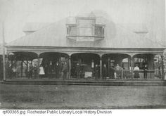 People are standing on the porch of the Glen Haven street car station. The location is E. Main Street at the corner of Chamberlain Street. The Glen Haven Line carried passengers to Irondequoit Bay.  Photo taken 1901 or 1909, view facing west.