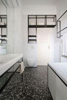 salle de bains blanche aménagée avec un sanitaire blanc, une étagère murale en métal noir et décorée d'une mosaïque