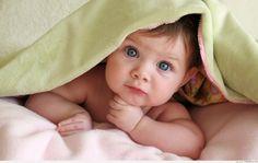 Một em bé tỏ ra dễ thương khi nằm dưới tấm chăn