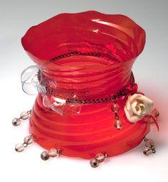 Una bottiglia rossa piena di brio prende la forma di un originalissimo bracciale. Rigido da infilare al braccio con deliziosi ciondolini e una rosellina riciclata da un vecchio bijou. Rijoux ha immaginato questa creazione per donne estrose e creative. Sempre uniche.