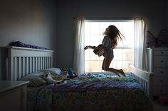 photo of girl jumping on her bed and playing the guitar by Jennifer Nobriga