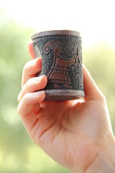 Viking shot glass with carved pattern of a Viking woman serving a beer from a drinking horn