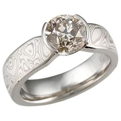 Mokume Solitaire Tapered Engagement Ring with Champagne Diamond - This simple yet enchanting ring has a Classic design with a Contemporary twist. The band has a uniform width until it intersects the head with an elegant taper. The setting tapers down to the band allowing for the unique engagement ring to sit flush next to a flat wedding band. - This well-proportioned ring has a 1.5 ct fancy champagne diamond and White mokume.