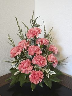 Pink Carnations with some fir branches and fatsia leaves - this type of floral arrangement will last for a couple of weeks.