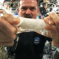 Two students wanted to know what happens when you wring out a water-soaked washcloth in zero gravity. Canadian astronaut Chris Hadfield was happy to oblige.