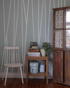 Ungefär en rulle maskeringstejp gick åt för fondväggen. För att inte färgen ska krypa in under tejpen måste man dra noga längs alla tejpkanter, med en spackel eller dylikt föremål. Rolla sedan hela väggen med en kontrasterande färg. || UnderbaraClara DIY accent wall, colour patterns, mask tape, pink, grey