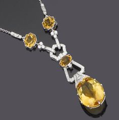 A citrine and diamond pendant necklace  The pear-shaped citrine drop suspended from a brilliant-cut diamond millegrain-set buckle motif, highlighted with calibré-cut citrines, to a trace-link chain, diamonds approx. 0.80ct. total, length 50.0cm. Art Deco or Art Deco style.