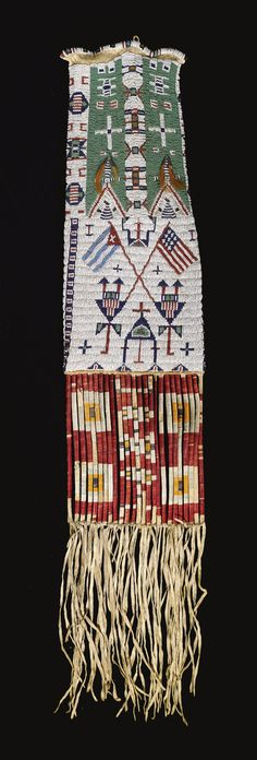 UNUSUAL SIOUX PICTORIAL BEADED HIDE TOBACCO BAG    elaborately stitched in opaque, translucent and faceted metal beadwork, with an American and Cuban flag on the front, the reverse, with typical geometric motifs, the cut hide panel below wrapped in dyed porcupine quillwork; trimmed with tin cone pendants inserted with horsehair.   length with fringe 38in.