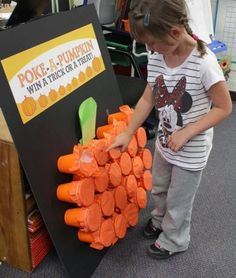 Great Halloween Game for all ages -Poke-A-Pumpkin - punch out the tissue paper on top a cup and find a Trick or a Treat inside! How fun!