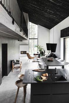 Sober ingerichte woonkamer met vide waar goed gebruik is gemaakt van diverse materialen zoals hout, kunststof en steen.