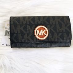 """MK Fulton Carryall Wallet Add a little luxury to your everyday accessory repertoire with this sleek and slim wallet. Retail at $138 in 2015, increased to $148 in 2016. My loss your gain. NWT. No trades!!  • Brown • 14 interior card slots  • Interior zip coin compartment • Two interior card slots • 7.5"""" x 4.5"""" x 1"""" • Magnetic fastening MICHAEL Michael Kors Bags Wallets"""