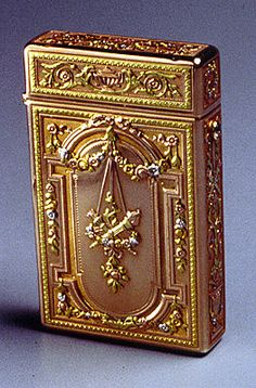 A four-color gold card-case in Louis XVI style chased with an archway, with, at its center, a monogram with a royal crown above. Applied with four-color gold floral swags suspended from rosettes, all on a yellow-gold sablé ground - signed Fabergé, initials of workmaster August Holmström, assay mark of St. Petersburg before 1899,