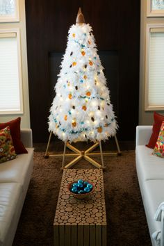 White feather boas, vintage blue tinsel garland, pinecones and dried orange slices made a special tree for this modern living room. An alternative Christmas tree by The Jubiltree Company cast a stunning glow at night.