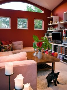 This living room features bright red walls as well as four windows, cozy seating areas, a low wood coffee table, a Flokati rug and a white shelving unit that is filled with books, art, copper dishes and a small TV.