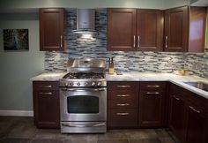 Here is our newly remodeled kitchen with a blue, glass backsplash, stainless steal range and range hood, with a grey porcelain tile floor and cherry wood cabinets