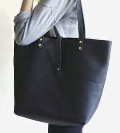 Crafted from thick, pebbled oil hide leather, this black tote bag is an excellent candidate for workhorse workbag, travel companion or everyday carryall.