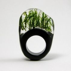 Ring made of black and clear resin with real moss embedded within it, by Sylwia Calus Design.