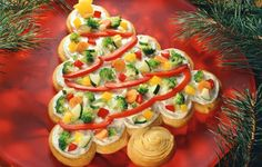 Vegetable Tree*2 cans  Pillsbury Crescent rolls*1 pkg cream cheese softened,1/2 c sour cream,1 tsp dried dill weed,1/8 tsp garlic powder,3 c assorted chopped vegetables, (bell peppers, broccoli, carrot, cucumber & green onion)Bake rolls as directed . Remove from oven 7 spread w/above mixture & decorate w/vegetables. Makes 2 trees.