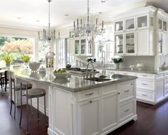 White kitchen cabinets; the glass-front smaller cabinets on top; countertops