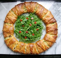 Niet alleen heel decoratief, maar ook heel lekker is deze hartig gevulde kerstkrans van croissantdeeg. Met een heerlijk gekruide kipvulling.