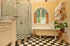 Love the yellow against the black and white tile, the claw foot tub, the window, the beadboard.....So Vintage