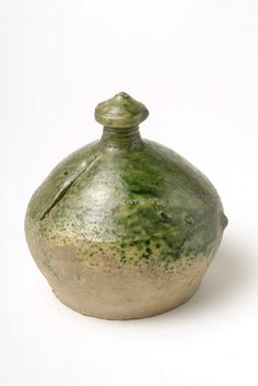 Green glazed border ware ceramic money box. Money boxes were thrown as an enclosed form with a boulbous body and moulded knop. This money box is slightly poited at the top and the coin slit is vertical and positioned at the upper body of the box. Money boxes are glazed externaly only and this example has a green glaze. Border ware ceramic pieces were produced in Surrey, Hampshire Border.