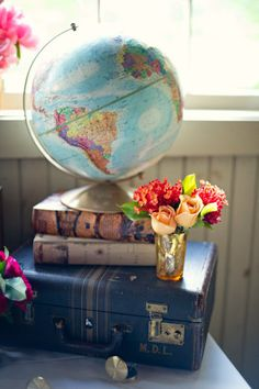 Love this globe sitting on old books and a suitcase. Could be a nice set-up for our global/Costa Rica themed wedding shower.