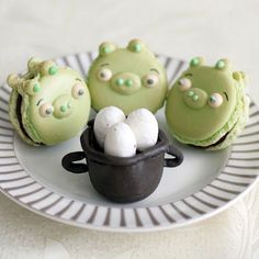 Cute green piggy macaroons from Angry Birds the game staring down a pot of eggs.