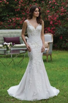Sincerity - Chickadee. A V-neck fit and flare tulle gown with beaded lace appliques, illusion back, horsehair hem, and chapel length train that create a classic wedding day look.