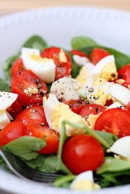 Halved cherry tomatoes, hard-boiled eggs quarters, salt and freshly ground pepper on a bed of baby spinach.