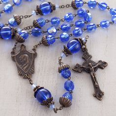 Czech Crystal Baroque Rosary, Sapphire Blue,  $52.95   The Catholic Company          Reminiscent of Mary's blue Mantle.. Sparkling Czech crystal beads. Unique antique bronze finish. Traditional and beautiful rosary.