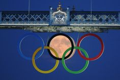 The full moon rises through the Olympic Rings hanging beneath Tower Bridge during the London 2012 Olympic Games (to see the olympics : bucket list) Full Moon Rising, Moon Rise, 3 Moon, Rising Sun, Moon Art, Optical Illusion Photography, Photo Illusion, Illusion Photos, Illusion Fotografie