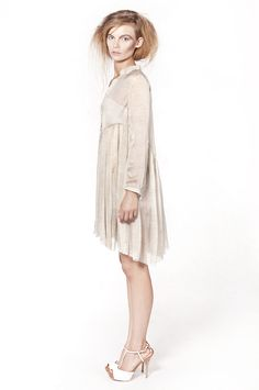 "This loose fit shirt-dress is from the ""Soroczki"" collection. A wide dress made of beige, transparent silk chiffon with metal buttons and a small skull button on the back arm."