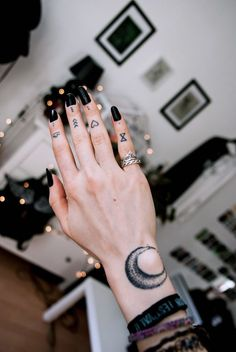 hand with different tattoos on each finger, black nail polish, finger tattoo, picture frames in the background