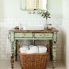 Farmhouse Restoration: Vintage Bathroom ~ Give a new room instant age.   A perfectly worn painted table breaks up the sea of white tile and carries on the farmhouse look.    Keep tile classic.   White subway-style tiles by Daltile pair with octagonal tiles on the floor. The charcoal-colored grout remains true to the period style.
