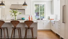 A pair of Thomas O'Brien Bryant Sconces illuminating a gray kitchen island lined with Cherner Counter Stools.