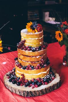 Naked wedding cake with thistle, sunflower and carnation, covered with fruits.