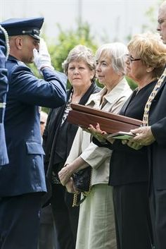 Col. Anthony Davit salutes as he presents an encased flag to Sue Scott, the sister of Capt. Douglas D. Ferguson, May 2, 2014, in Lakewood, Wash. Ferguson's F-4D aircraft was shot down over Laos in 1969, and his remains were returned home after being missing for more than 44 years. Davit is the 627th Air Base Group commander. (U.S. Air Force photo/Tech. Sgt. Sean Tobin)