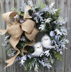 In this Christmas and wintertime wreath, a lovely burlap bow and a pair of adorable owls are the focal point. Snowy boughs of mixed greenery create