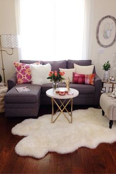 In this room the pop of bright color from 2 pillows is accentuated by the grey and white colors surrounding them. White is a bright color too. In this case it is positioned on every surface in this room. The white coffee table (from HomeGoods) helps visually in making this vignette feel complete and anchors the space. Sponsored by HomeGoods