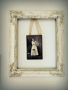 Charming...distressed white frame with small picture hung with ribbon.