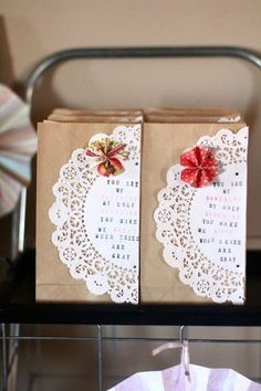 Doily decorated brown paper bags for party.