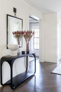 Beautiful entryway design with black modern table and framed mirror