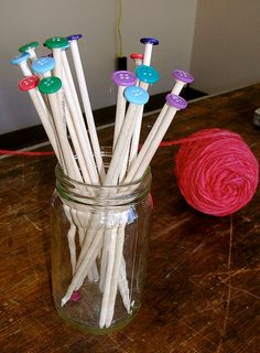 DIY Knitting Needles: Take wooden dowels, sharpen the working ends with a pencil sharpener, sand down the points a bit, and hot glue buttons to the base.