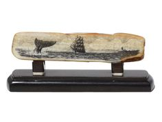 """Off to Work"" Black and White Scrimshaw on Ancient Walrus Tusk Ivory by Gerry Dupont. A whaler is seen just leaving port, passing by the last lighthouse they will see for months and months. The average whaling voyage lasted three years. Long day at the office. Really nice piece of fossil walrus on this one. Ebony stand really sets it off. Size: 4 3/4""L x 1 1/4""D x 1 3/4""H    -- on ScrimshawGallery.com #scrimshaw"